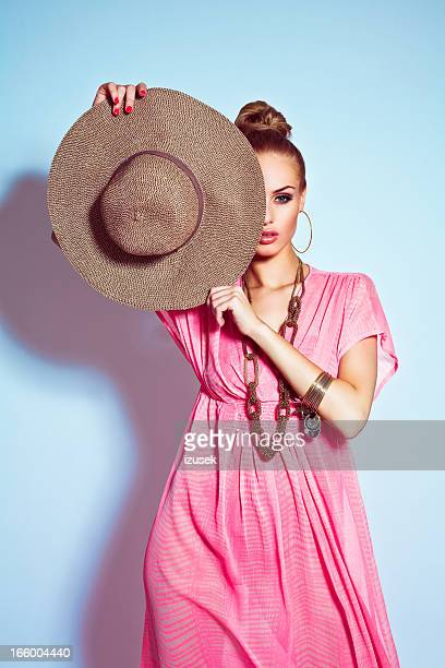 glamour portrait of woman posing with sun hat - pink dress stock photos and pictures