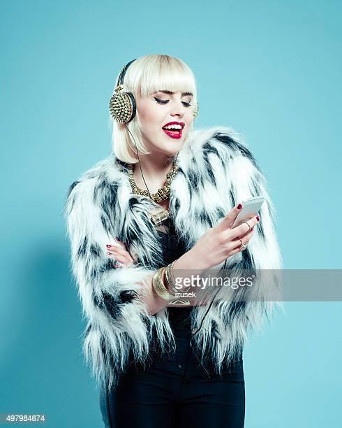 Glamour woman wearing fur jacket and gold jewlery using phone