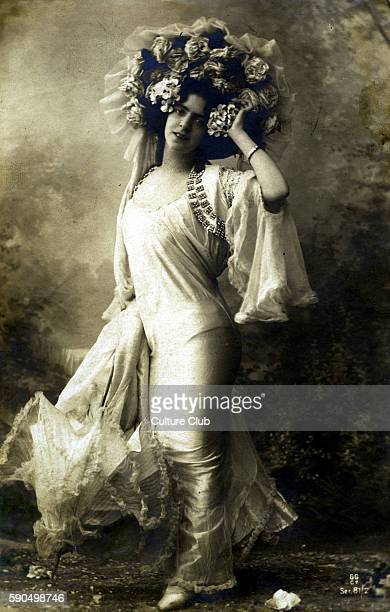 Glamourous dress, early 20th century. Woman in a satin dress, with a jewelled shrug jacket with long flowing sleeves, accessorised with a decorative...
