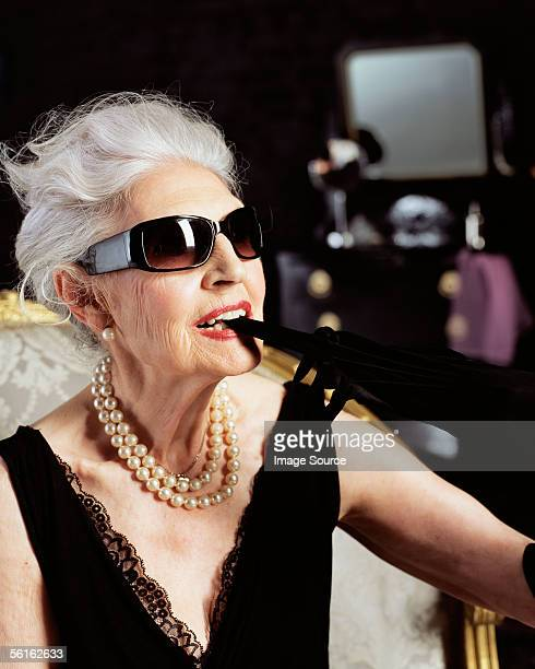glamourous senior woman biting glove - grey dress stock pictures, royalty-free photos & images