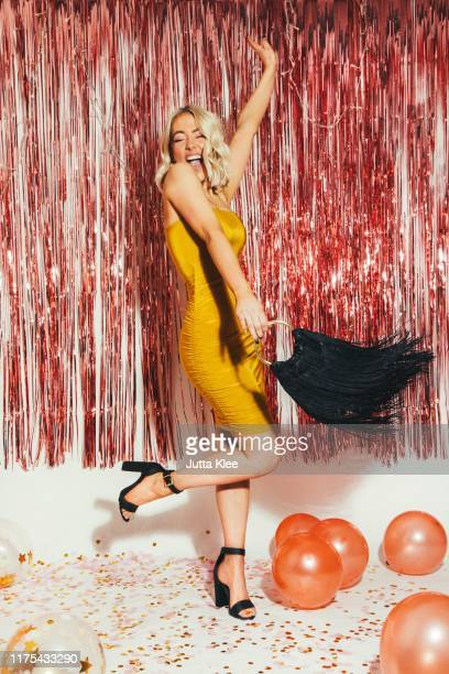 glamourous young women posing at party with handbag - fringe dress stock pictures, royalty-free photos & images