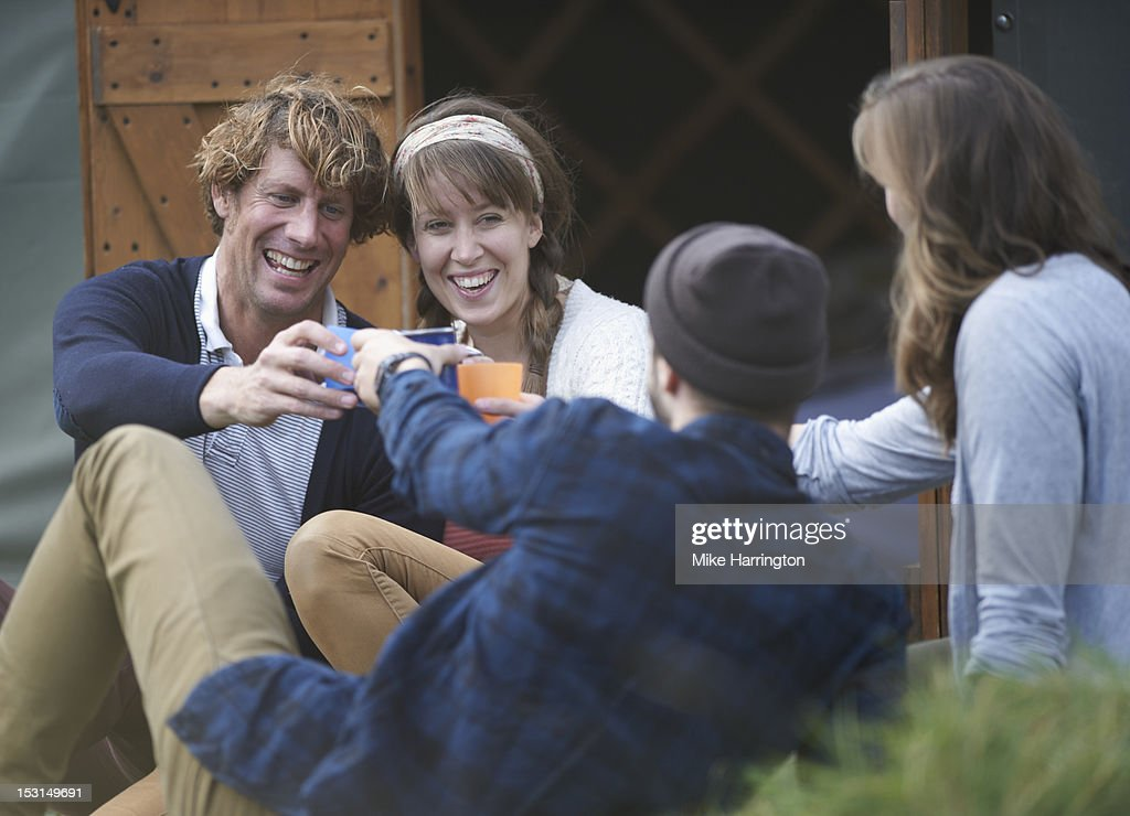 Glamping couples outside yurt sharing a toast. : Foto de stock