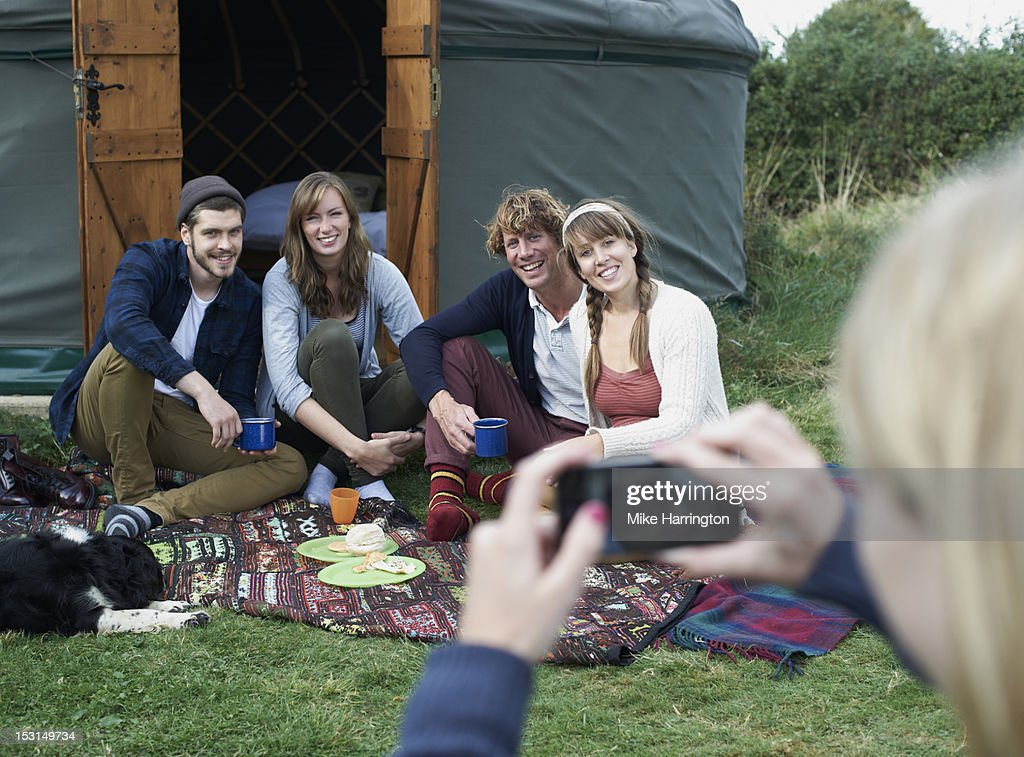 Glamping friends on rug posing for photograph. : Stock Photo