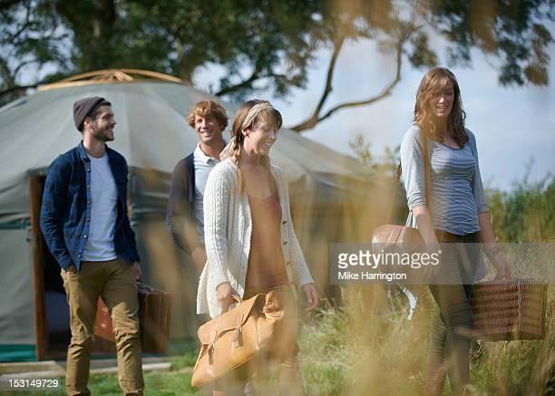 Glamping young people walking outside yurt.