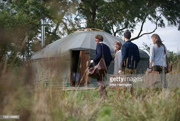 Glamping young people walking towards yurt.