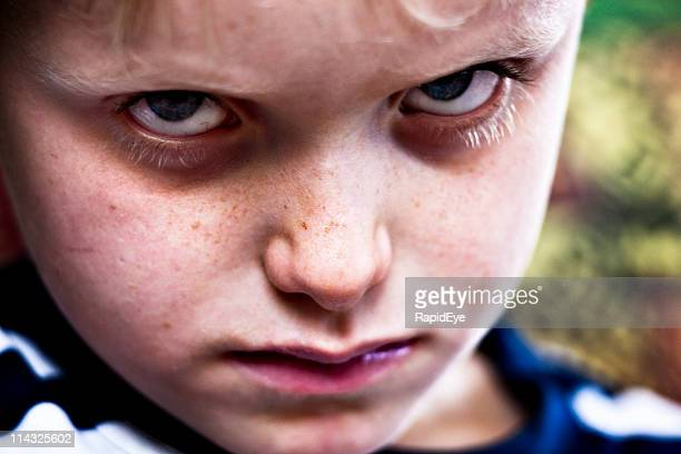 Glaring child | Boy looks sulky, cross, hostile