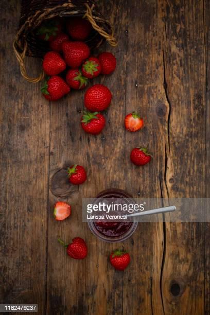 glas of homemade strawberry jam, strawberries, on dark wood - larissa veronesi stock-fotos und bilder