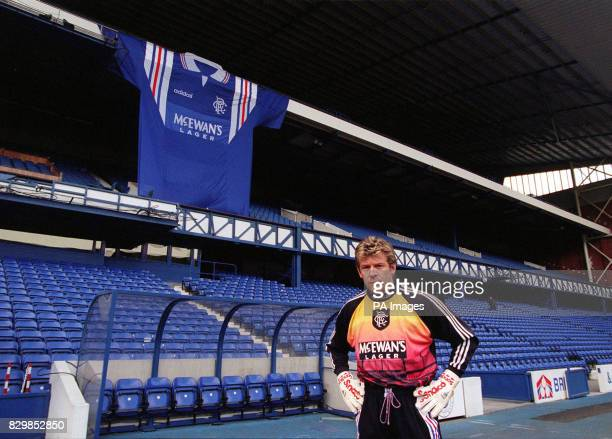 Glasgow Rangers' goalkeeper Andy Goram models the club's new strip at the club's ground Ibrox today while a giant version of the Scottish Premier...