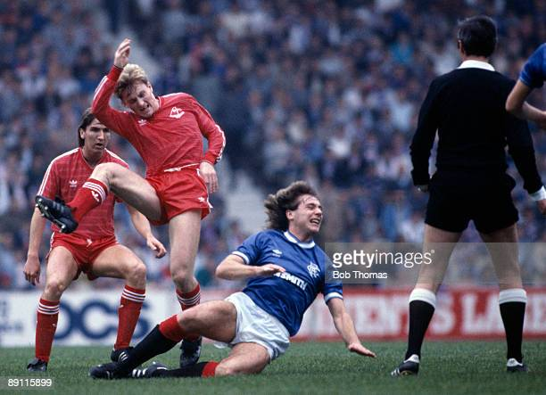 Glasgow Rangers striker Ally McCoist slides in to tackle Aberdeen's Stuart McKimmie with Brian Mitchell looking on during the match at Ibrox Stadium...