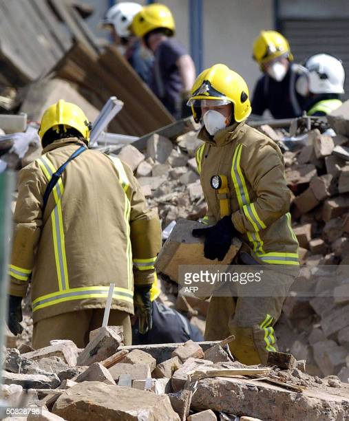 Firemen clear debris from the collapsed Stockline Plastics factory after the building exploded in Glasgow 12 May 2004 Scores of people were injured...