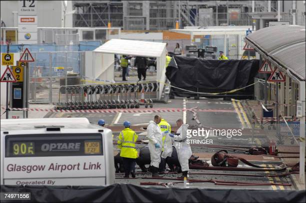 Forensics investigate 01 July 2007 the area where a burning car slammed into a terminal at Glasgow airport a day after the attack Glasgow airport was...