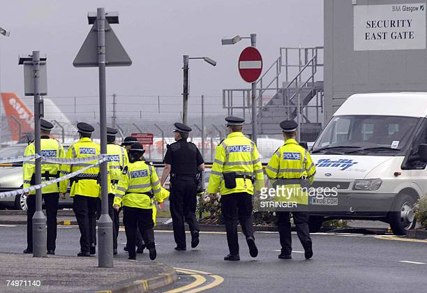 Police officers walk oustide Glasgow airport which was partially reopened 01 July 2007 less than 24 hours after an attack in which a burning car was...
