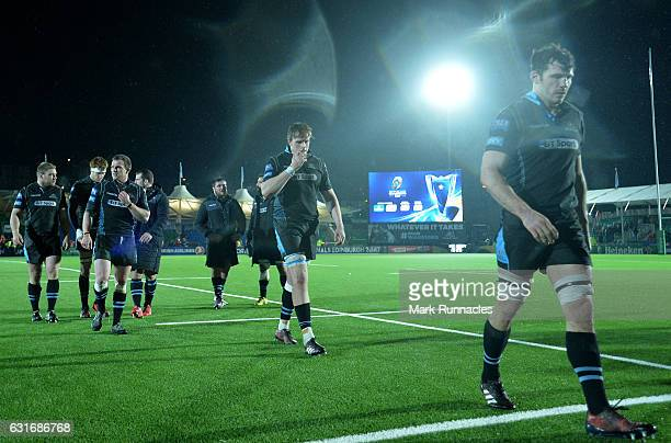 Glasgow Warriors players walk from the pitch at the final whistle as they lose 1412 to Munster Rugby during the European Rugby Champions Cup match...