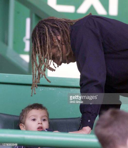 Crocked Celtic star Henrik Larsson makes sure son Jordan is comfy before settling down to watch the game