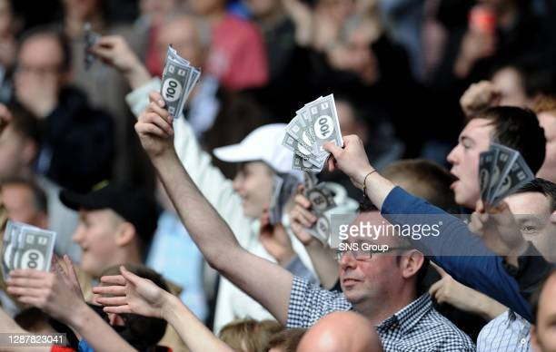 Fans display fake money during the match.