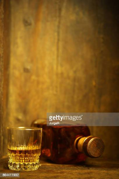 ein glas und eine flasche whisky auf hölzernen hintergrund - bourbon whiskey stock-fotos und bilder