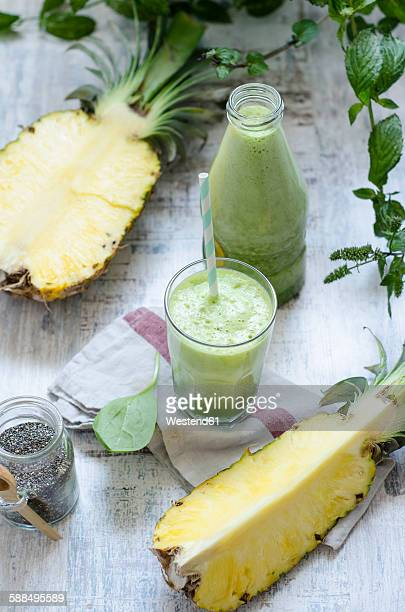 Glass and bottle of spinach pineapple smoothie with chia and mint