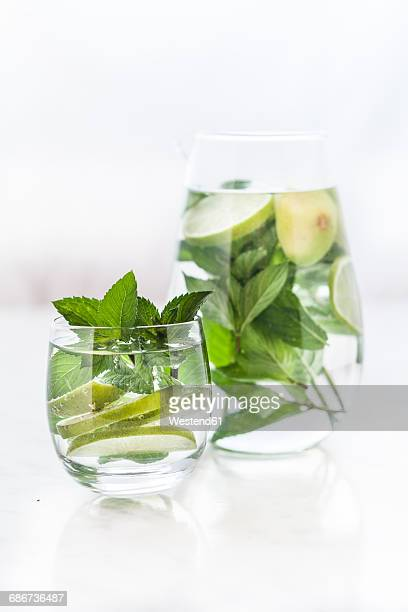 Glass and carafe of detox water with mint and limes