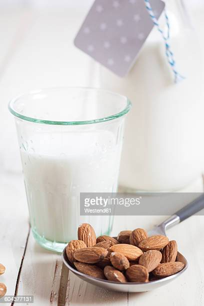 Glass and carafe of homemade almond milk and almonds