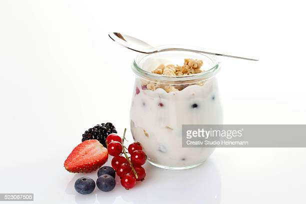 Glass and spoon with muesli, yoghurt, berries, red currants, blueberries, strawberry, blackberry