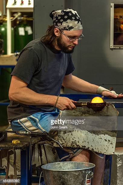 Glass artisan working with molten glass