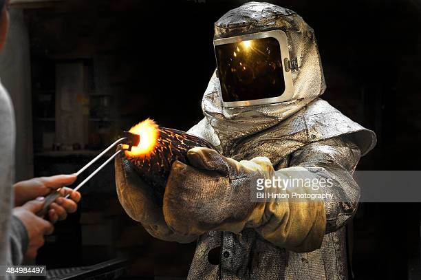 glass artist working in protective suit - bill hinton stock pictures, royalty-free photos & images