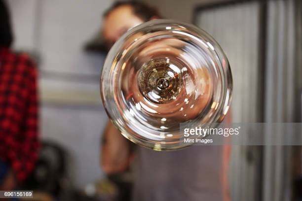 A glass at the end of a tube, a glassblower at work.