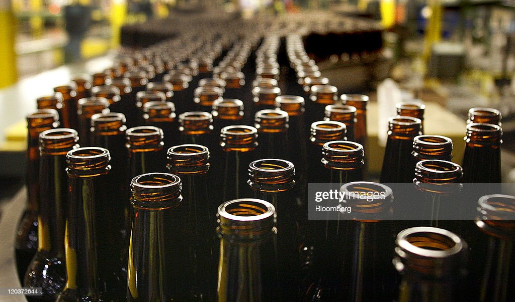 Glass beer bottles move down a conveyor belt at the Owens-Illinois Inc. glass manufacturing plant in Waco, Texas, U.S., on Thursday, Aug. 4, 2011. Owens-Illinois Inc., the world's largest glass container manufacturer, delivers safe, effective and sustainable glass packaging solutions to a growing global marketplace. Photographer: Mike Fuentes/Bloomberg via Getty Images