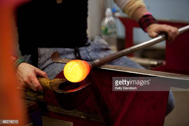 Glass blower sculpting molten glass