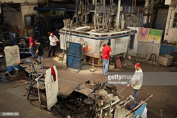 Glass blowers working in glass factory