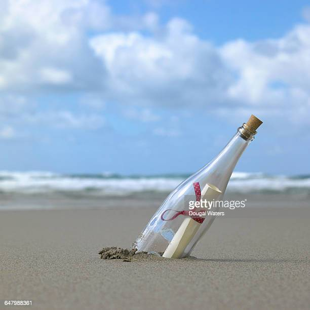 Glass bottle in sand at beach with message inside.