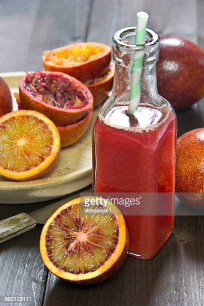 Glass bottle of blood orange juice, whole, sliced and squeezed blood oranges