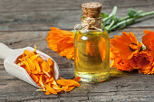 Glass bottle of calendula essential oil with fresh marigold flowers on wooden table