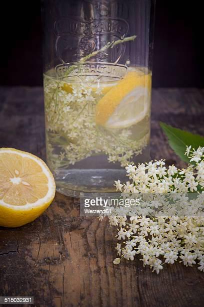 Glass bottle of elderflower sirup, elderflower and half of lemon on dark wood