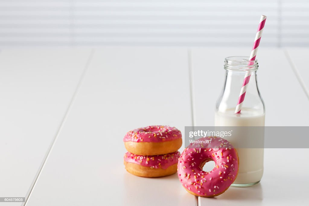 Glass bottle of milk and three doughnuts with pink icing on white ground : ストックフォト