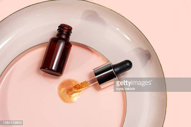 glass bottle of oil with a pipette or face serum on a pastel pink background with sunlight. - cbd oil stock pictures, royalty-free photos & images