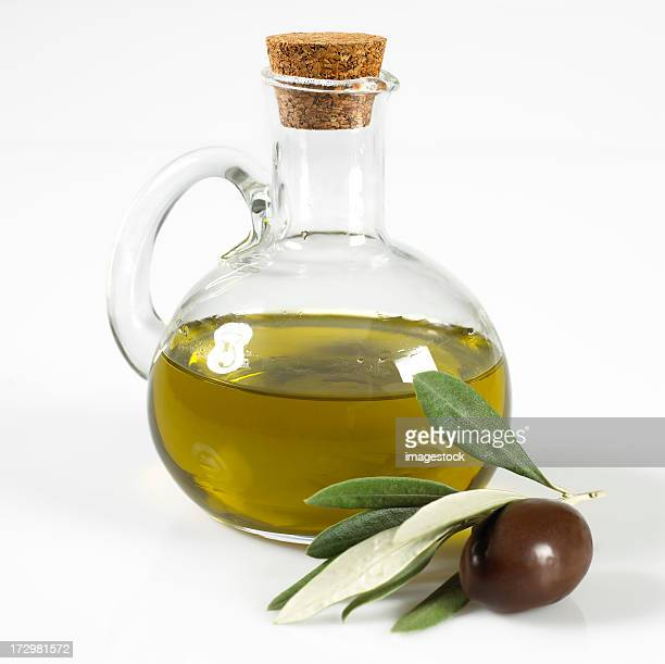 Glass bottle of olive oil and fresh olive