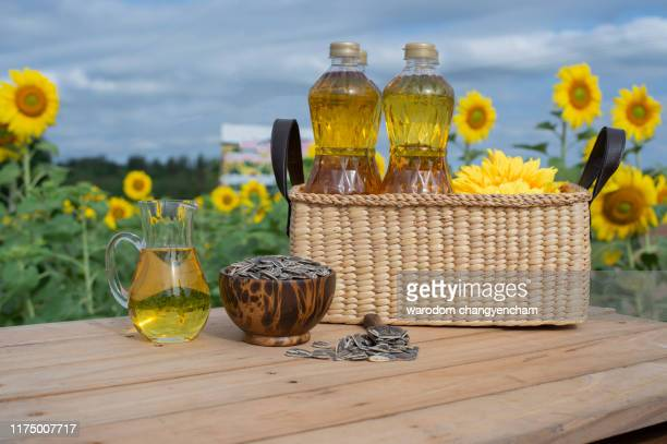 glass bottle of sunflower oil with seeds and flowers. close up view with copy space on table wooden background. - black seed oil stock pictures, royalty-free photos & images