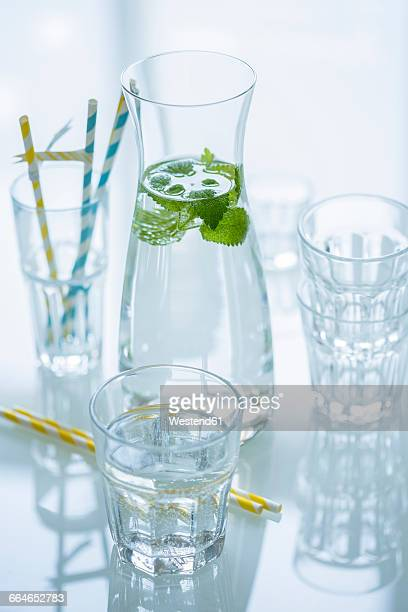 Glass bottle of water flavored with lemon balm and different glasses