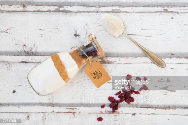 Glass bottle with ingredients of baking mix for cranberry chocolate cake