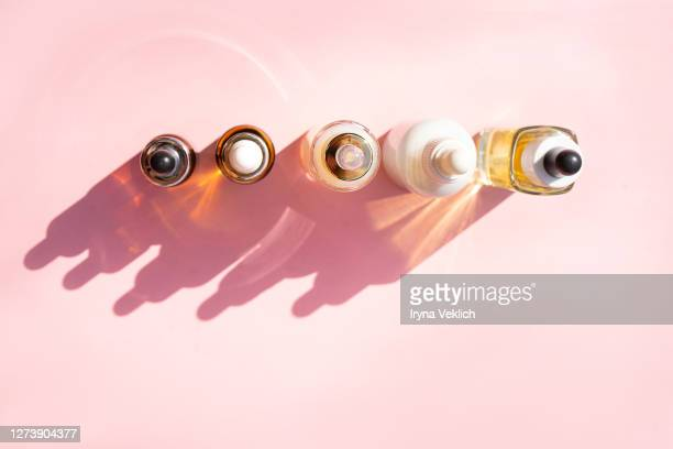 glass bottles of beauty serum with shadows on pastel pink background. - cbd oil stock pictures, royalty-free photos & images
