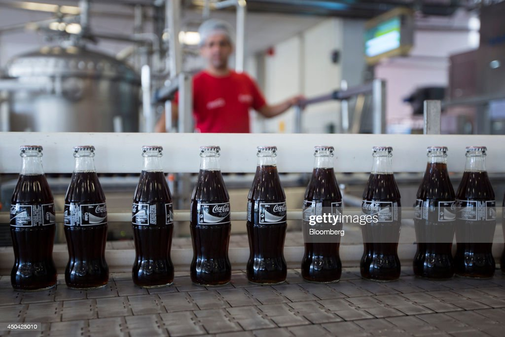 Glass bottles of Coca-Cola Light, also known as diet Coke, move along the production line after filling at the Lanitis Bros Ltd. bottling plant, part of the Coca-Cola Hellenic Group, in Nicosia, Cyprus, on Tuesday, June 10, 2014. Zug, Switzerland-based Coca-Cola Hellenic Bottling Co., which distributes Coca-Cola products in countries including Russia, wants to move away from using imported sugar for its Russian operations by 2015. Photographer: Andrew Caballero-Reynolds/Bloomberg via Getty Images