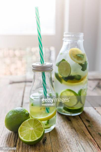 Glass bottles of infused water with lemon, lime, mint leaves and ice cubes