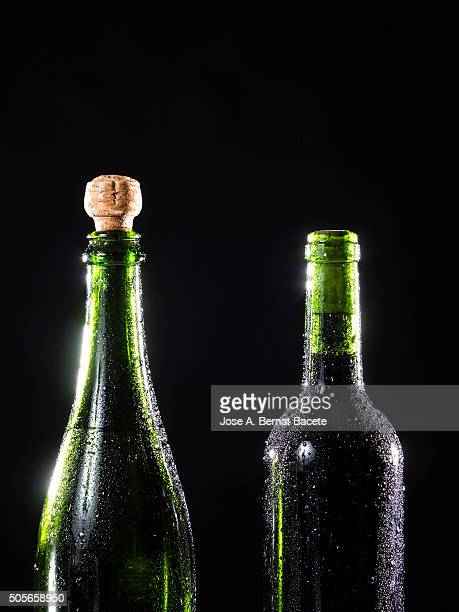 Glass bottles of wine and wine-cellar with drops of cold water
