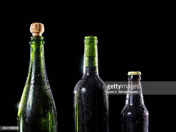 Glass bottles of wine, beer and wine-cellar with drops of cold water