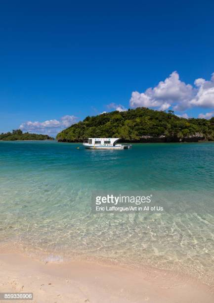 Glass bottom boat in the tropical lagoon beach with clear blue water and white sand surrounded by lush greenery in Kabira bay Yaeyama Islands...