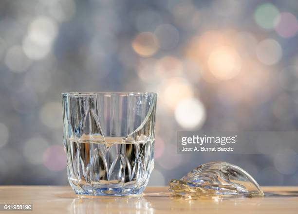Glass bowl broken with water, on a wooden table, illuminated by sunlight