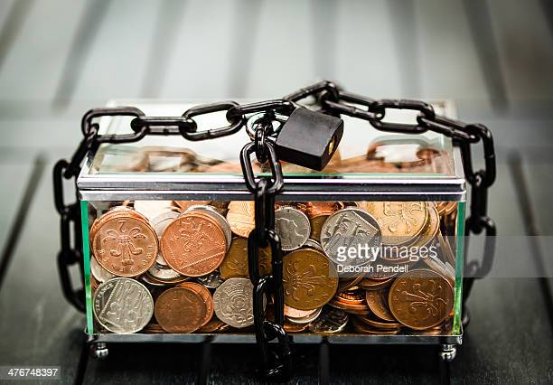 Glass box of money with padlock and chain