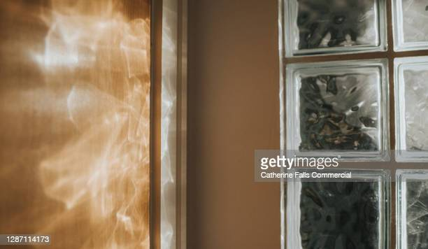 glass bricks creating lighting effect against a wall - sun stock pictures, royalty-free photos & images