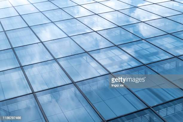 glass building under blue sky and white clouds - tour structure bâtie photos et images de collection